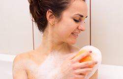 Mujer joven que se lava con la esponja en el baño Fotos de archivo libres de regalías