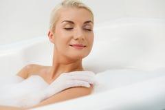 Mujer joven que se lava en cuarto de baño Foto de archivo libre de regalías