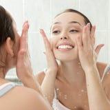 Mujer joven que se lava la cara con el agua potable Foto de archivo