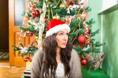 Mujer joven que se pregunta sobre el regalo de los regalos de Navidad y del Año Nuevo Fotografía de archivo libre de regalías