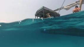 Mujer joven que se prepara para zambullirse del barco de madera almacen de video