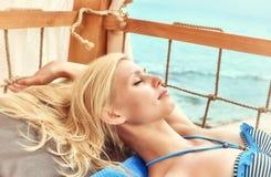 Mujer joven que se reclina por el mar Imagen de archivo libre de regalías