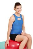 Mujer joven que se reclina sobre bola del ejercicio Foto de archivo libre de regalías
