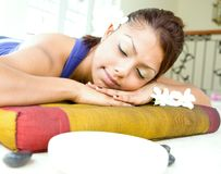 Mujer joven que se reclina sobre cama del masaje Foto de archivo libre de regalías