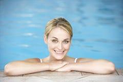 Mujer joven que se reclina sobre el borde de la piscina Fotos de archivo libres de regalías