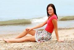 Mujer joven que se reclina sobre la playa Imagenes de archivo