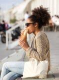 Mujer joven que se relaja al aire libre y que come la comida Fotografía de archivo libre de regalías