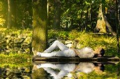 Mujer joven que se relaja cerca del agua en pontón Fotografía de archivo