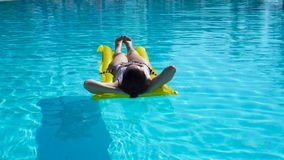 Mujer joven que se relaja con el colchón de aire en piscina del aire libre almacen de video
