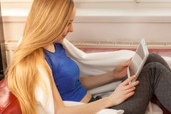 Mujer joven que se relaja con la tableta Imágenes de archivo libres de regalías