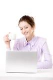 Mujer joven que se relaja con la taza de café delante del ordenador portátil Foto de archivo libre de regalías
