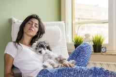 Mujer joven que se relaja en casa abrazando su pequeño perro Fotografía de archivo