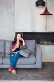Mujer joven que se relaja en casa con un vidrio de zumo de naranja La muchacha hermosa en un estilo sport se sienta en el sofá y  Fotos de archivo