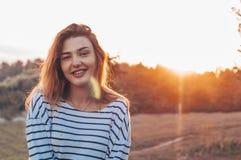 Mujer joven que se relaja en cielo de la puesta del sol del verano Retrato de la mujer joven hermosa hecha excursionismo en la pu foto de archivo