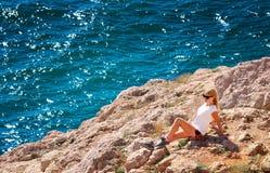 Mujer joven que se relaja en el acantilado rocoso con el mar azul en fondo Foto de archivo
