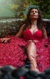 Mujer joven que se relaja en el baño al aire libre de la flor, cuidado de piel orgánico, balneario de lujo en selva Cuidado de la foto de archivo