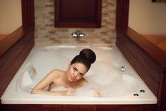 Mujer joven que se relaja en el balneario del baño del Jacuzzi de la espuma, goce moreno Fotografía de archivo
