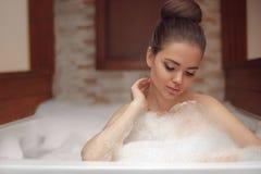 Mujer joven que se relaja en el balneario del baño del Jacuzzi de la espuma, goce moreno Fotografía de archivo libre de regalías