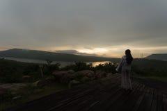 Mujer joven que se relaja en el cielo de la puesta del sol del verano al aire libre Fotos de archivo