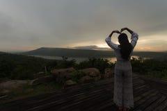 Mujer joven que se relaja en el cielo de la puesta del sol del verano al aire libre Imágenes de archivo libres de regalías