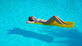Mujer joven que se relaja en el colchón de aire en piscina del aire libre almacen de video