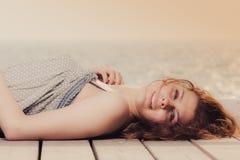 Mujer joven que se relaja en el embarcadero al aire libre fotografía de archivo libre de regalías