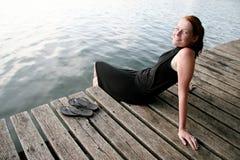 Mujer joven que se relaja en el lago Fotografía de archivo