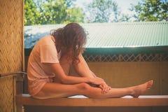 Mujer joven que se relaja en el pórtico Foto de archivo libre de regalías
