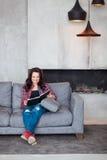 Mujer joven que se relaja en el país La muchacha hermosa en un estilo sport se sienta en el sofá y lee un libro en el hogar del e Imagen de archivo libre de regalías
