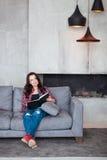 Mujer joven que se relaja en el país La muchacha hermosa en un estilo sport se sienta en el sofá y lee un libro en el hogar del e Imagen de archivo