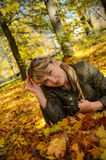 Mujer joven que se relaja en el parque brillante del otoño Foto de archivo