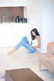 Mujer joven que se relaja en el piso en una sala de estar Foto de archivo libre de regalías