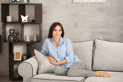 Mujer joven que se relaja en el sofá imagenes de archivo