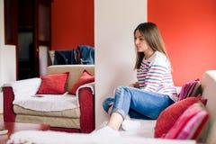 Mujer joven que se relaja en el sofá Fotos de archivo