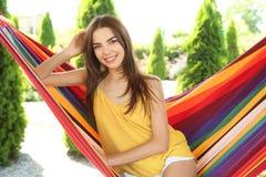 Mujer joven que se relaja en hamaca al aire libre el día de verano imagenes de archivo