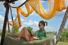 Mujer joven que se relaja en hamaca con la tableta Fotografía de archivo libre de regalías