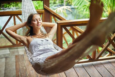 Mujer joven que se relaja en hamaca en un centro turístico tropical Fotografía de archivo libre de regalías