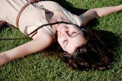 Mujer joven que se relaja en hierba Fotos de archivo