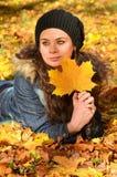 Mujer joven que se relaja en hojas de otoño Imágenes de archivo libres de regalías