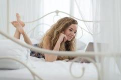 Mujer joven que se relaja en la cama con el ordenador portátil Fotografía de archivo