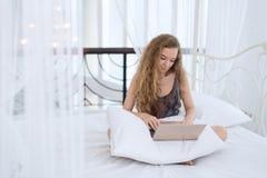 Mujer joven que se relaja en la cama con el ordenador portátil Imagenes de archivo