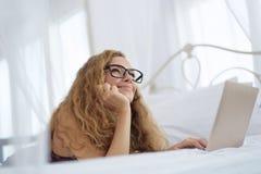 Mujer joven que se relaja en la cama con el ordenador portátil Imagen de archivo libre de regalías