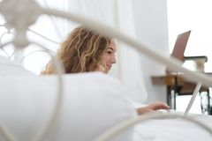 Mujer joven que se relaja en la cama con el ordenador portátil Foto de archivo libre de regalías
