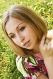 Mujer joven que se relaja en la hierba Imagen de archivo