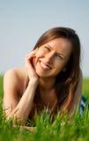 Mujer joven que se relaja en la hierba Fotos de archivo