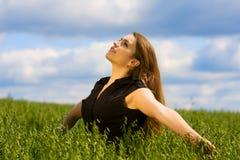 Mujer joven que se relaja en la naturaleza. Foto de archivo