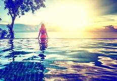 Mujer joven que se relaja en la piscina, cerca del mar en la puesta del sol Imagenes de archivo