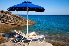 Mujer joven que se relaja en la playa. Foto de archivo