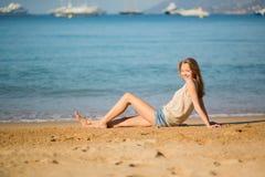 Mujer joven que se relaja en la playa Fotografía de archivo