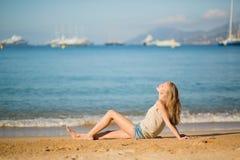 Mujer joven que se relaja en la playa Imagenes de archivo